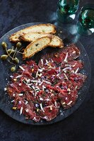 Beef carpaccio with pine nuts, grated cheese, edible flowers, capers and bread