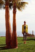 Junge Frau in buntem Shirt, Caprihose und gelbem Blazer