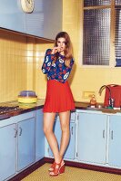 Junge Frau in gemustertem Pulli und rotem Minirock steht in Küche