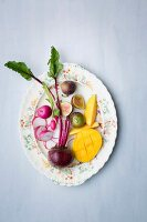 Fresh radishes, beetroot, mango and figs on a plate (seen from above)