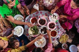 A Thai family eating various dishes, Mae Hong Son, Thailand