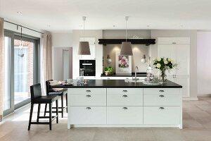 weiße Kücheninsel mit schwarzer Arbeitsplatte, seitlich Barhocker mit Lederbezug