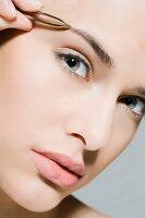 Frau zupft mit Pinzette Augenbraue