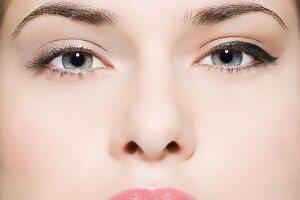 Gesicht einer jungen Frau mit unterschiedlich geschminkten Augen