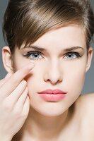 Junge Frau mit Kontaktlinse auf dem Finger