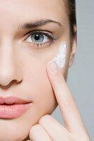 Junge Frau beim Auftragen von Gesichtscreme