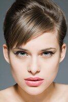 Geschminkte junge Frau mit Hochsteckfrisur