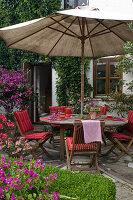 Terrasse am Haus mit Holz - Sitzgruppe und Sonnenschirm