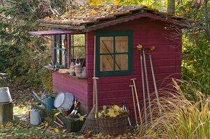Rotes Gartenhaus mit grünen Fenstern im herbstlichen Garten