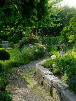 Mauer aus Granit-Blöcken, Weg aus Schotter, Staudenbeete mit Paeonia