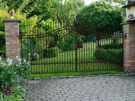 Blick in den Garten durch schmiedeeisernes Tor