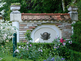 Sichtschutzmauer mit Bacchus-Kopf und Pflanzgefäßen