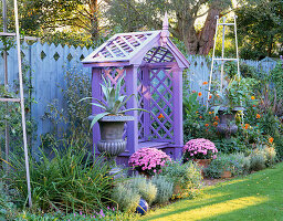 NICHOLS Garden: COVERED WOODEN SEAT SURROUNDED by Silver PAINTED Metal STANDS AND TWO URNS PLANTED with AGAVES. IN TWO POTS ARE Pink CHRYSANTHEMUMS. NICHOLS Garden, READING