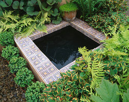PATTERNED TILES SURROUND SMALL POND with MATTUECIA STRUTHIOPTERIS, GUNNERA AND ASPLENIUM. BRINSBURY COLLEGE'S COURTYARD Garden, CHELSEA