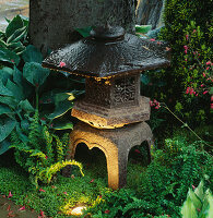 JAPANESE STONE LANTERN LIT UP AND SURROUNDED by HOSTAS AND FERNS IN THE 'ZEN INSPIRED' Garden DESIGNED by SPIDERGARDEN.COM, LIGHTING by COTSWOLD ELECTRICAL. CHELSEA