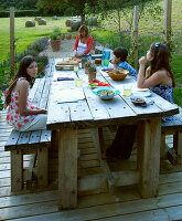 Designer Clare MATTHEWS: Devon GARDEN. OUTDOOR SEATING AREA. WOODEN TABLE AND BENCHES On PATIO. Clare AND CHILDREN ABOUT TO EAT LUNCH