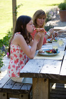 Designer Clare MATTHEWS: Devon GARDEN. OUTDOOR SEATING AREA. WOODEN TABLE AND BENCHES On PATIO. Clare AND CHILDREN EATING LUNCH