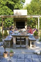 Clare MATTHEWS Garden, DEVON. Clare AND FAMILY SIT DOWN TO an Al Fresco LUNCH at THE OUTDOOR Dining TABLE. Pergola, OUTDOOR OVEN. DINING. Designer Clare MATTHEWS