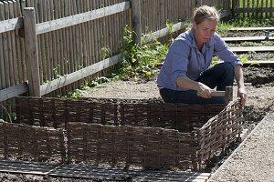 Frau schlägt Beeteinfassung aus Weide in die Erde