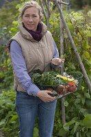 Frau mit frisch geerntetem Gemüse im Drahtkorb