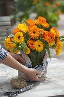 Strauss aus Calendula (Ringelblumen), Vase mit Geschirrtuch verkleiden
