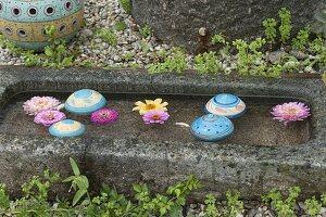 Getoepferte Schwimmkugeln schwimmen in Granit-Trog