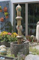 Säule aus getoepferten Elementen als Wasserspiel in Granit-Kübel