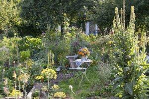 Kleiner Sitzplatz zwischen Beeten mit Stauden und Sommerblumen