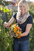 Frau pflückt Strauss von Sommerblumen mit essbaren Blüten