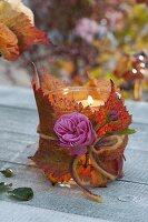 Glas umwickelt mit Blättern von Brombeere (Rubus) als Windlicht
