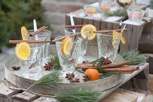 Leere Gläser für Punsch, Orangenscheiben (Citrus), Zimtstangen, Sternanis