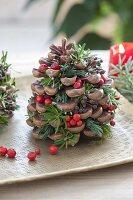 Zapfen von Pinus (Pinie) gefüllt mit roten Beeren von Ilex (Stechpalme)