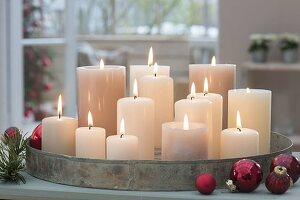 Metall-Tablett mit weissen Kerzen, rote Baumkugeln daneben