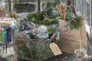 Drahtkorb mit Zapfen, Zweigen von Abies (Tanne), Gläser mit Samen