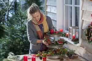 Adventsdeko mit Kerzen und Scheinbeeren in Metall-Etagere