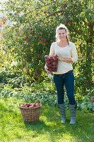 Frau bei der Apfelernte im Garten