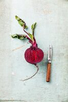 Ripe beetroot with leaves on textured background