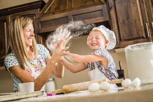 A mother and daughter having a food fight with flour in the kitchen