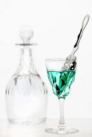 Absinthe with an absinthe spoon in a crystal glass in front of a crystal carafe of water