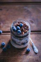 Chocolate granola and yogurt breakfast jar topped with blueberries