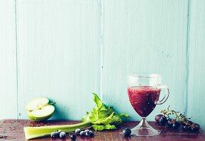 Cassis-Drink mit Apfel, Staudensellerie und Trauben