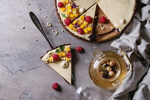 Homemade sliced chocolate tart and piece of tart decorated by mango, raspberries, mint, puffed rice and edible flowers