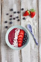 A smoothie bowl with strawberries, blueberries and coconut chips