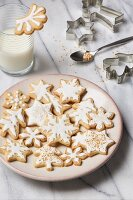 Glazed butter cookies, a glass of milk, and various cookie cutters