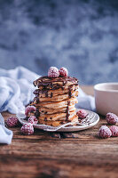 Stack of banana pancakes topped with chocolate drizzle and frozen raspberries