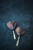 Heart-shaped vegan biscuits on sticks covered with dark chocolate and sprinkles