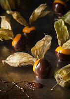 Physalis with chocolate icing on a metal surface