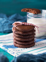 Stack of home made chocolate cookies with red twine over green background