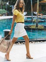 Junge Frau in gelbem T-Shirt und weißem Rock