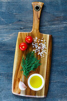 Rural wooden kitchen table with cutting board and ingredients on vintage background